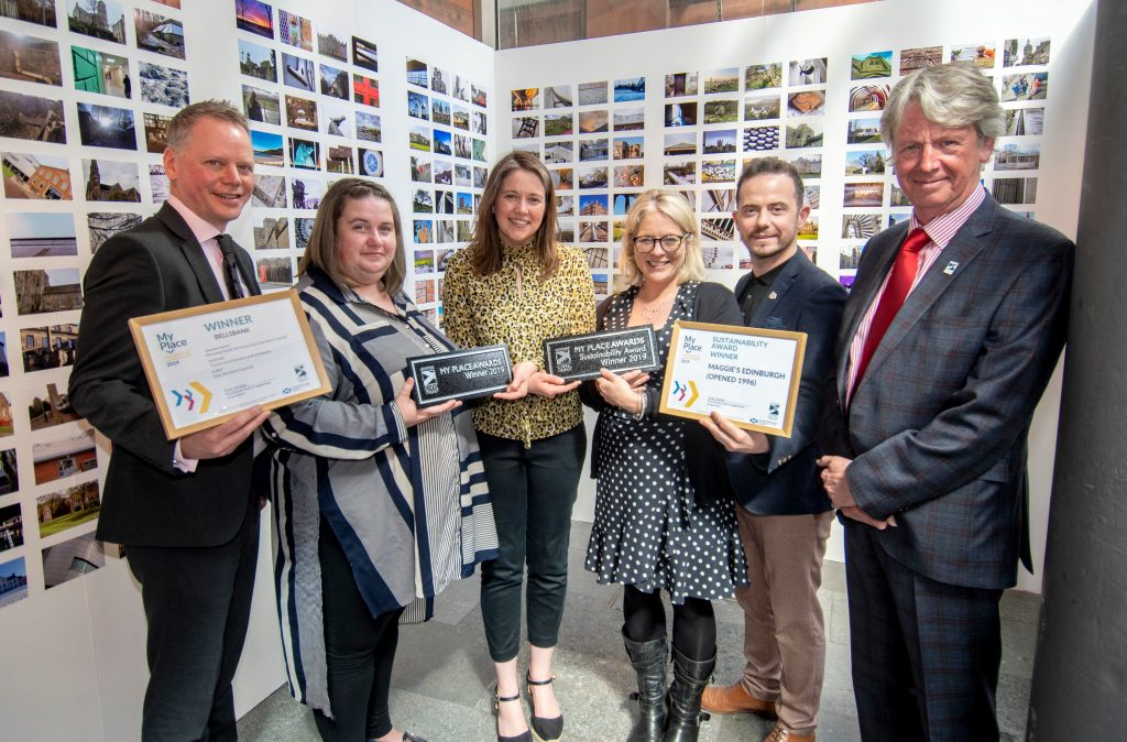 Representatives from the My Place Award and Sustainability Award winning projects stand with Aileen Campbell MSP and Colin McLean, Chair, SCT. They smile and are holding their certificates and plaques, in the background is a photo wall.