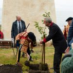 Lord Lyon planting tree. He put in first spade of soil then invited school children to complete the planting
