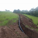 2 pipe being laid in fields