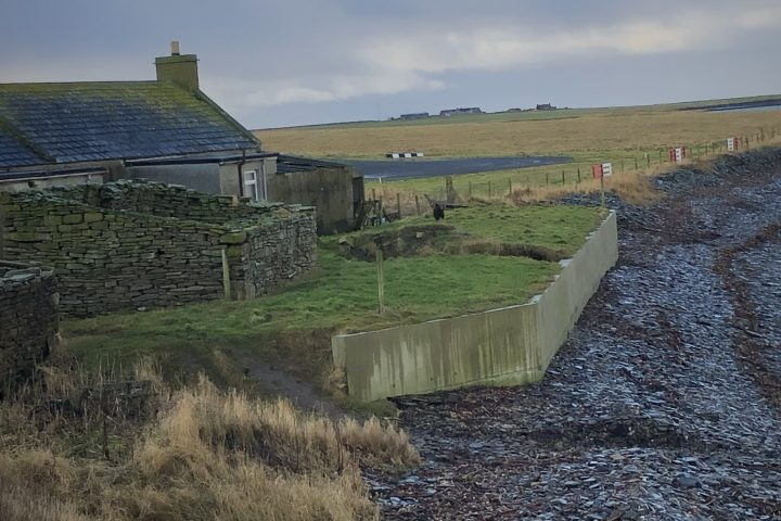 A concrete wall protecting a house from the sea